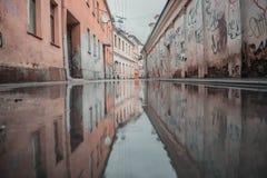 Riflessione dell'acqua di una via in vecchia città Kaunas immagini stock