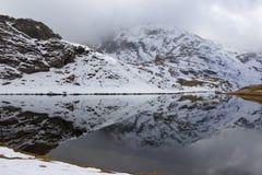 Riflessione dell'acqua Lago alpino & x28; Palasina& x29; in un giorno nuvoloso e nebbioso in autunno Fotografia Stock Libera da Diritti