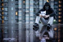 Riflessione dell'uomo di maglia con cappuccio di mistero con la maschera nera che tiene maschera bianca che si siede nella pioggi fotografia stock libera da diritti