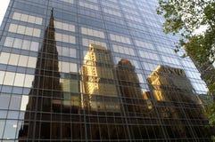 Riflessione della chiesa e di parecchie costruzioni nelle finestre del grattacielo immagini stock libere da diritti