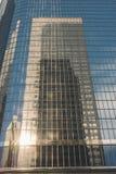 Riflessione della costruzione della ruspa spianatrice del cielo su tutta la costruzione di vetro immagine stock