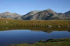 Riflessione della cresta della montagna in un lago Immagine Stock