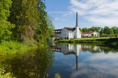 Riflessione della distilleria di Palmse in acqua dello stagno fotografia stock