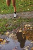 Riflessione della giovane donna in una pozza di acqua in parco Immagine Stock