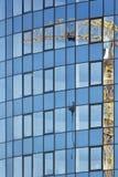 Riflessione della gru di costruzione sul vetro dell'edificio per uffici a più piani alto Immagini Stock