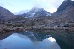 Riflessione della montagna in acqua con le nuvole Fotografia Stock