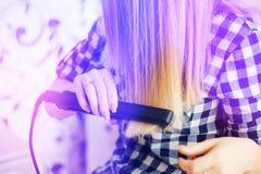 Riflessione della ragazza nello specchio, che fa il parrucchiere dei capelli , tonalità leggera immagini stock