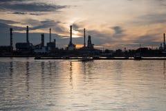 Riflessione della riva del fiume e dell'acqua della raffineria di petrolio Fotografia Stock