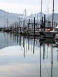 Riflessione delle barche con la montagna su fondo in Seward Fotografia Stock