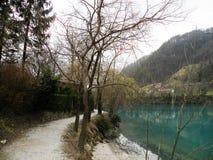 Riflessione delle colline, delle montagne, del villaggio e del cielo in acqua del turquise immagine stock
