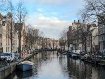 Riflessione delle costruzioni di mattone fiamminghe tradizionali del duch famoso di Amsterdam sul canale in Olanda, Paesi Bassi fotografie stock