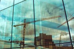 Riflessione delle costruzioni e delle gru, gente di camminata in grandi glas Fotografia Stock