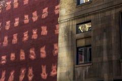Riflessione delle finestre sulla parete esterna del mattone e dell'edificio per uffici commerciale di pietra nella città fotografie stock libere da diritti