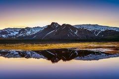 Riflessione delle montagne di inverno al tramonto in un lago Immagine Stock
