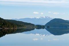 Riflessione delle montagne di Snowy in un lago - isola di Vancouver, BC, il Canada fotografie stock