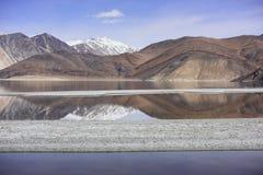 Riflessione delle montagne sul lago Pangong con il fondo del cielo blu Leh, Ladakh, India Fotografia Stock