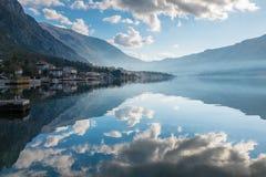 Riflessione delle nuvole con il fondo delle montagne Fotografia Stock