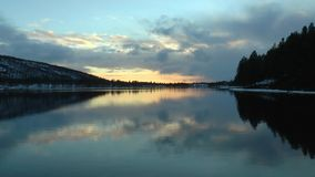 Riflessione delle nuvole di sera leggermente nel preoccupare la superficie del lago archivi video
