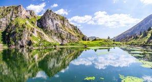 Riflessione delle nuvole nell'acqua del lago dell'alta montagna Immagini Stock Libere da Diritti