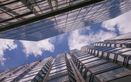 Riflessione delle nuvole in pareti di vetro dei grattacieli nella grande città e nel cielo blu con le nuvole bianche fotografia stock libera da diritti