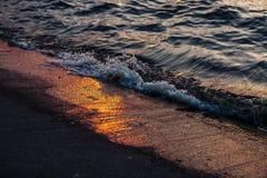 Riflessione delle onde e del sole della spuma nel porto di Nida lithuania fotografia stock