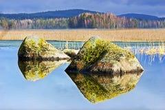 Riflessione delle rocce su un lago calmo Fotografia Stock