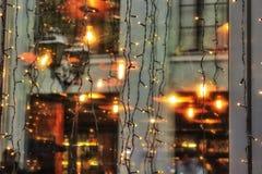 Riflessione di architettura, luci nel Natale, finestre del negozio del nuovo anno, sulle finestre, finestre, asfalto bagnato immagine stock