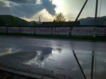 Riflessione di cielo blu dopo pioggia con le belle nuvole scure e leggere in una pozza immagini stock
