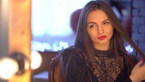 Riflessione di giovane bella donna che applica il suo trucco, guardante in una giovane donna splendida dello specchio 4 K con bel archivi video