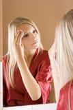 Riflessione di giovane donna di blone che rimuove trucco Fotografia Stock