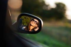 Riflessione di giovane ragazza mora splendida in occhiali da sole in uno specchio laterale di un'automobile fotografia stock libera da diritti