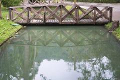 Riflessione di piccolo ponte di legno nello specchio liscio Fotografie Stock Libere da Diritti