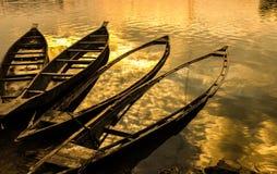 Riflessione di sera del cielo sulle barche abbandonate Fotografia Stock