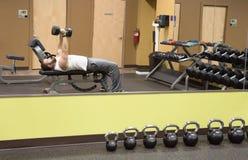 Riflessione di sollevamento pesi in specchio con Kettlebells Immagini Stock