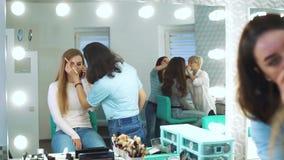 Riflessione di specchio del truccatore che fa trucco professionale per la giovane donna sveglia al salone di bellezza stock footage