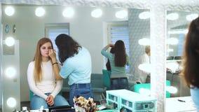 Riflessione di specchio del truccatore femminile che applica i cosmetici sulla giovane donna al salone di bellezza archivi video