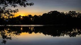 Riflessione di tramonto di sera con Starburst Fotografia Stock
