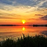 Riflessione di tramonto in lago calmo Immagine Stock
