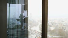 Riflessione di un uomo che cammina sulla pedana mobile all'alta palestra del pavimento con la grande vista della città con traffi video d archivio