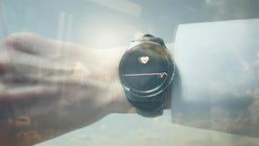Riflessione di un uomo che controlla il suo impulso su uno smartwatch stock footage