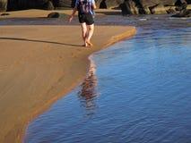 Riflessione di un viaggiatore con zaino e sacco a pelo e delle orme sulla sabbia Fotografie Stock Libere da Diritti