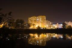 Riflessione di una città di notte nell'acqua fotografie stock