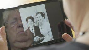 Riflessione di una donna senior che esamina le vecchie foto su un computer della compressa video d archivio