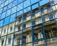 Riflessione di vecchia casa e del cielo con le nuvole nelle finestre il nuovo Immagine Stock