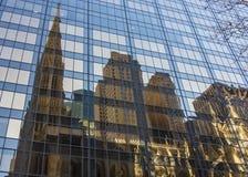 Riflessione di vecchie chiesa e costruzione di pietra marroni nel vetro o Fotografia Stock