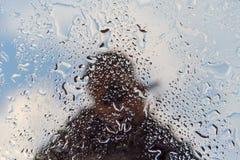 Riflessione irriconoscibile della siluetta dell'uomo su una finestra bagnata fotografia stock