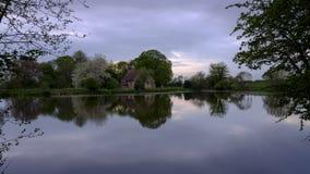 Riflessioni della chiesa di St Leonard in Hartley Mauditt Pond, bassi del sud parco nazionale, Regno Unito fotografie stock