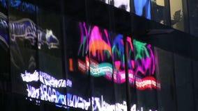 Riflessioni della pubblicità al neon principale nelle finestre di vetro archivi video