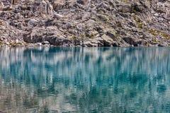 Riflessioni delle rocce sul lago dell'alta montagna Fotografia Stock Libera da Diritti