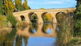 Riflessioni di vecchio ponte di pietra storico nelle acque del fiume del carbone immagini stock libere da diritti